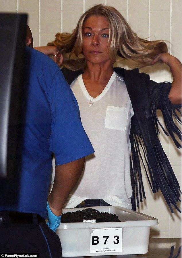 Quick scan: A TSA official appeared to make a search of LeAnn Rimes' carry on items as she flew out of LAX on Monday