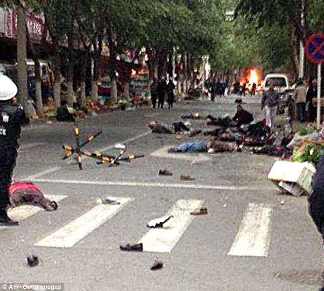 Victims of a bombing lie on a street near the site where attackers ploughed two vehicles into a market