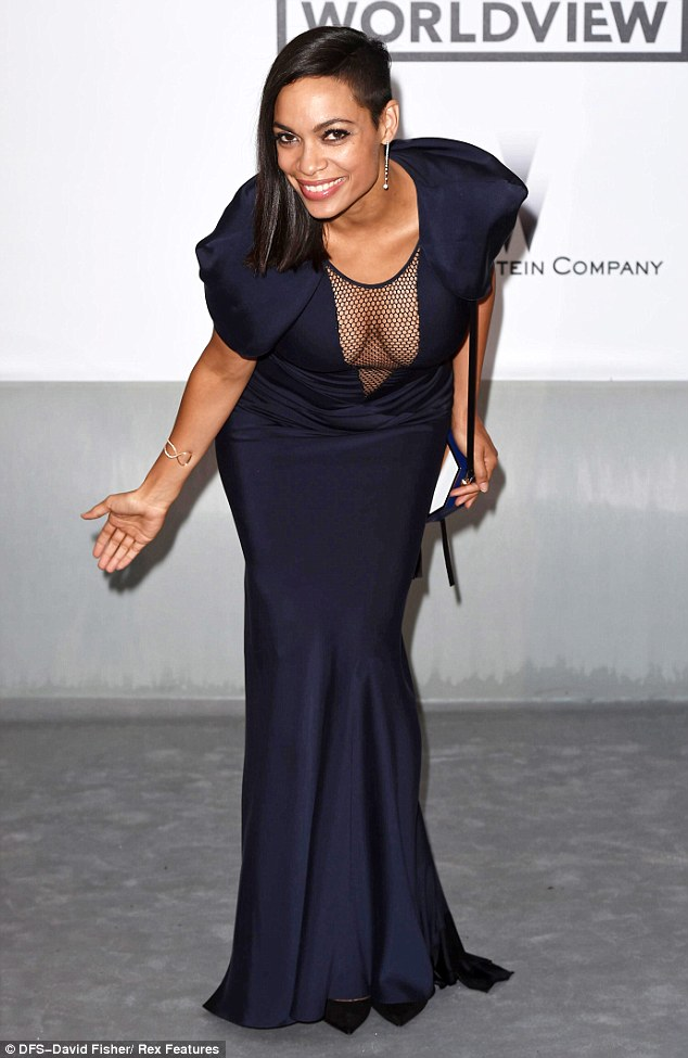 Rosario Dawson reveals her gym honed figure in a backless blue gown with sheer net panel as she dazzles at amfAR gala