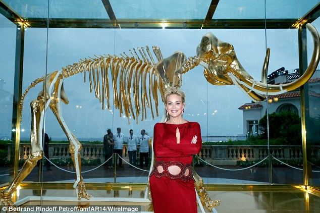 Bones: Sharon proudly posed before a gilded woolly mammoth skeleton donated by artist Damien Hirst for the auction