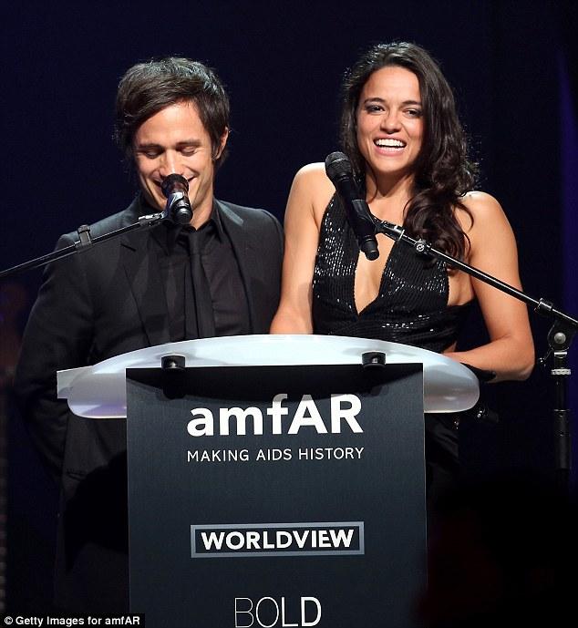 Risos Gael García Bernal (L) e Michelle Rodriguez, que tinha deixado seu cabelo feito spoke falar no palco)