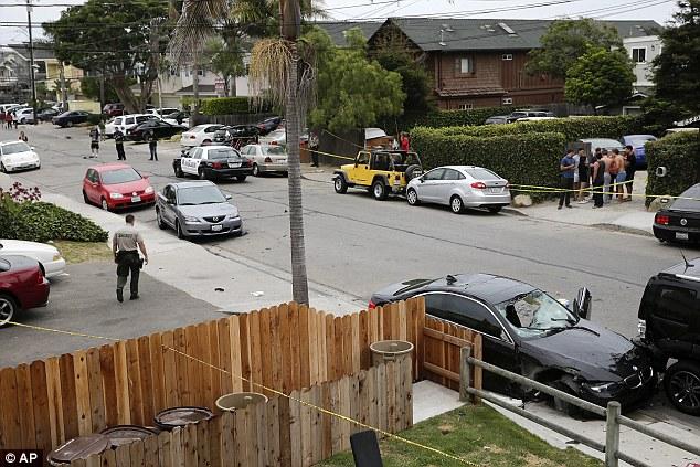 Aftermath: A deputy sheriff walks near a black BMW sedan driven by a drive-by shooter on Saturday, May 24, 2014, in Isla Vista, California near a Santa Barbara university campus