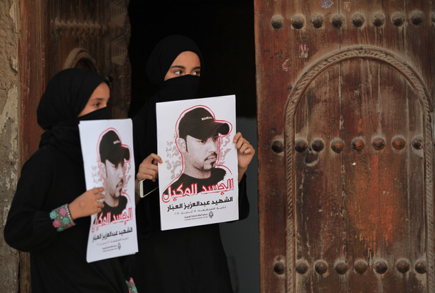 Bahraini girls hold posters of a protester who died last month from injuries sustained during clashes with police before a small protest march in Diraz, Bahrain, Friday, May 23, 2014 (AP Photo/Hasan Jamali)