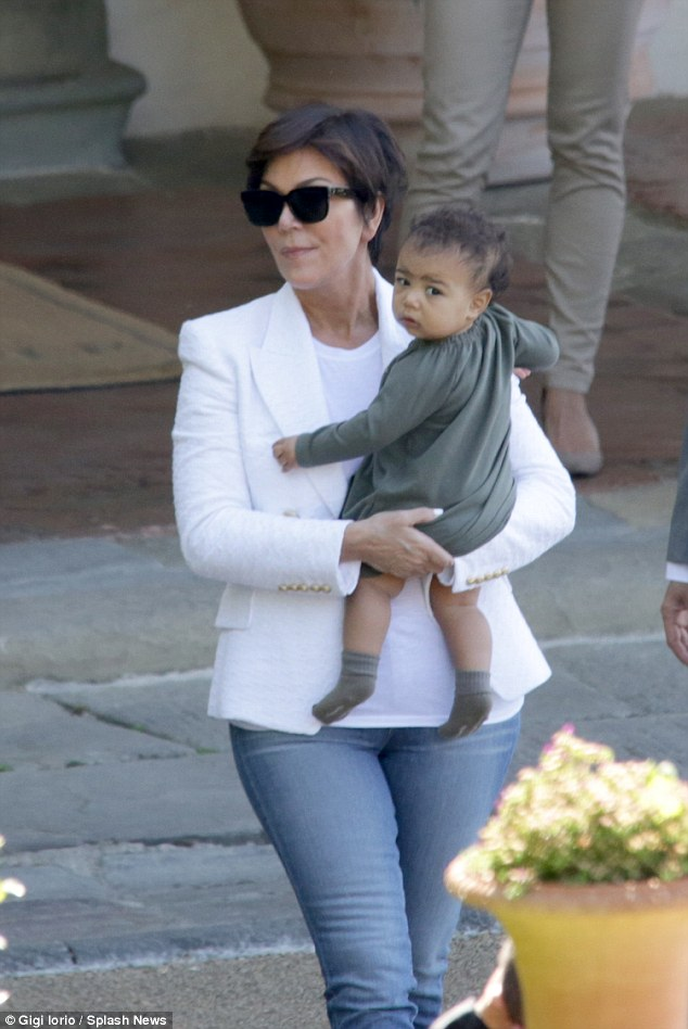 Supergran! Kris Jenner cradles baby North as she heads to Firenze airport in Florence on Sunday after attending daughter Kim Kardashian and Kanye West's wedding