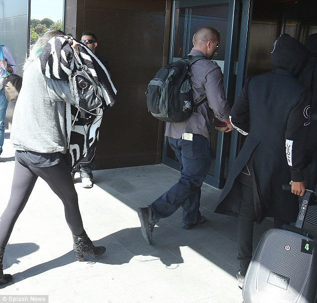 Disguising themselves: Kylie covered her face with a blanket as she walked into the airport while sister Kendall kept her hood up