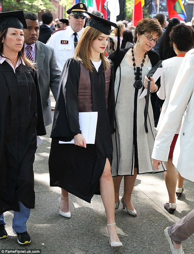 Protection: Emma Watson (centre) was accompanied by an undercover armed police guard (left) as she graduated from Brown University on Sunday