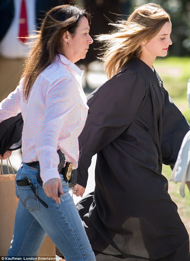 Extra security: The policewoman (left) wore a pink shirt and blue jeans, which her police badge was attached to, but she later blended in with the graduates by changing into a traditional cap and gown