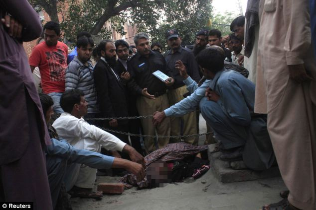 Police collect evidence near the body of Farzana Parveen, who was killed after being set upon by members of her own family outside a court in Lahore