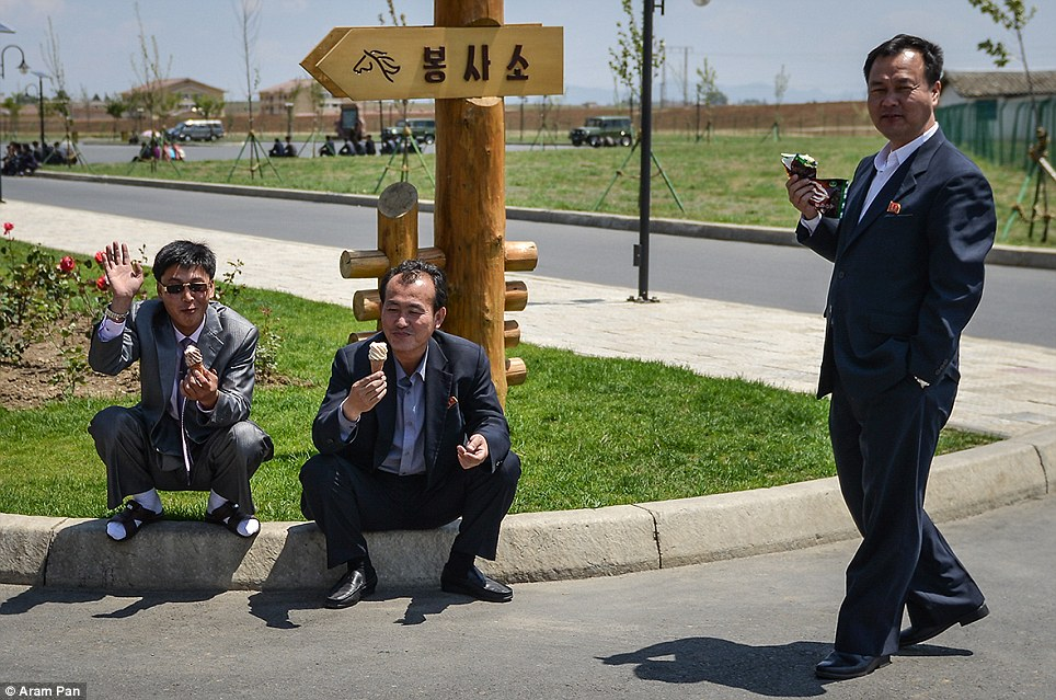 North Korean men wearing suits enjoy ice cream in the sunshine, contradicting the most commonly cited cliche that North Korea is a 'destitute, starving country'. One man perches on a kerb and waves in his white socks and sandals