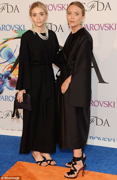 Identical style: Identical twins Mary Kate and Ashley Olsen chose almost identical outfits of long black coat dresses and sandals with clutch bags and event styled their hair similarly for the occasion