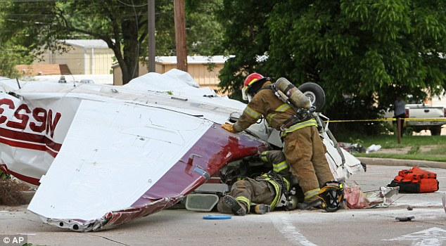 Firefighters inspect the Beechcraft Bonanza airplane that crashed into the parking lot of the McDonald's