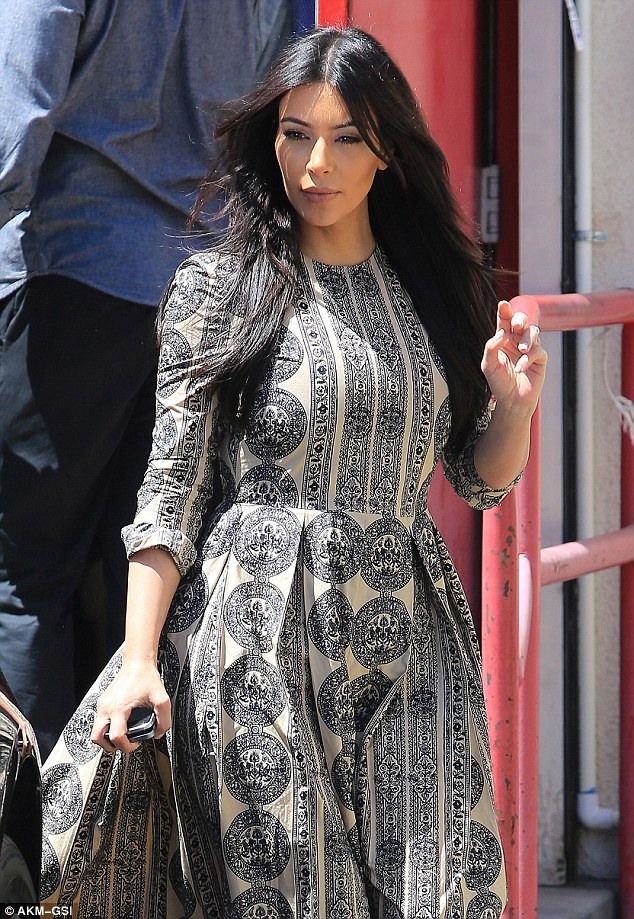 No handbag? Kim carried just her cellphone, forgoing accessories to allow her unusual dress to take center stage