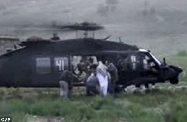 Final check: He is briefly frisked again before climbing aboard the helicopter as he is led by the arm