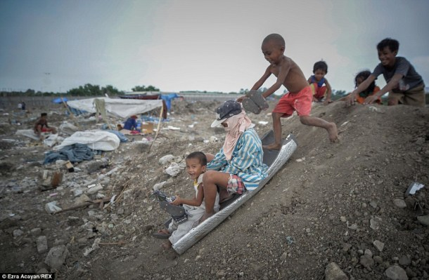 Children play along a slope at a garbage dump during World Environment Day