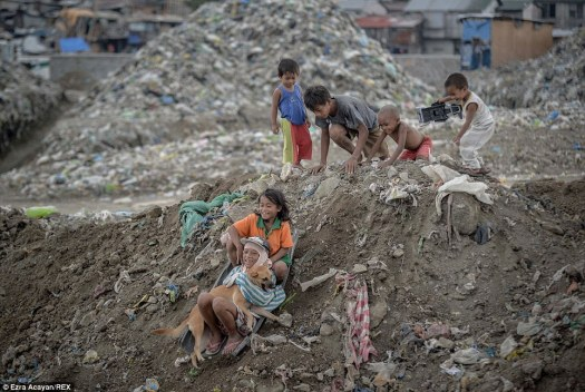 It might be hard work - but they can still find something to smile about. Children play along a slope at the garbage dump