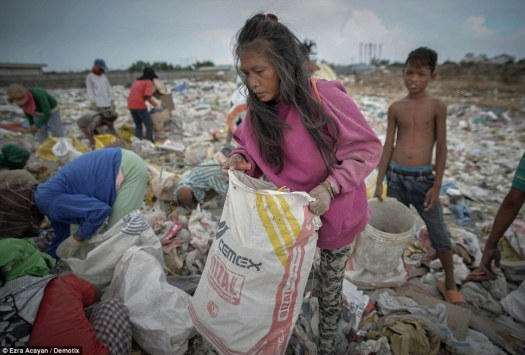An elderly woman looks for recyclables at a garbage dump during UN World Environment Day in, Paranaque, south of Manila, Philippines