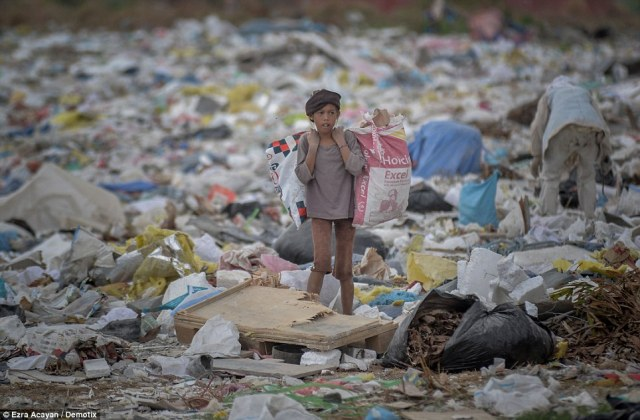 A young girl carries two bags as she looks through the rubbish dump