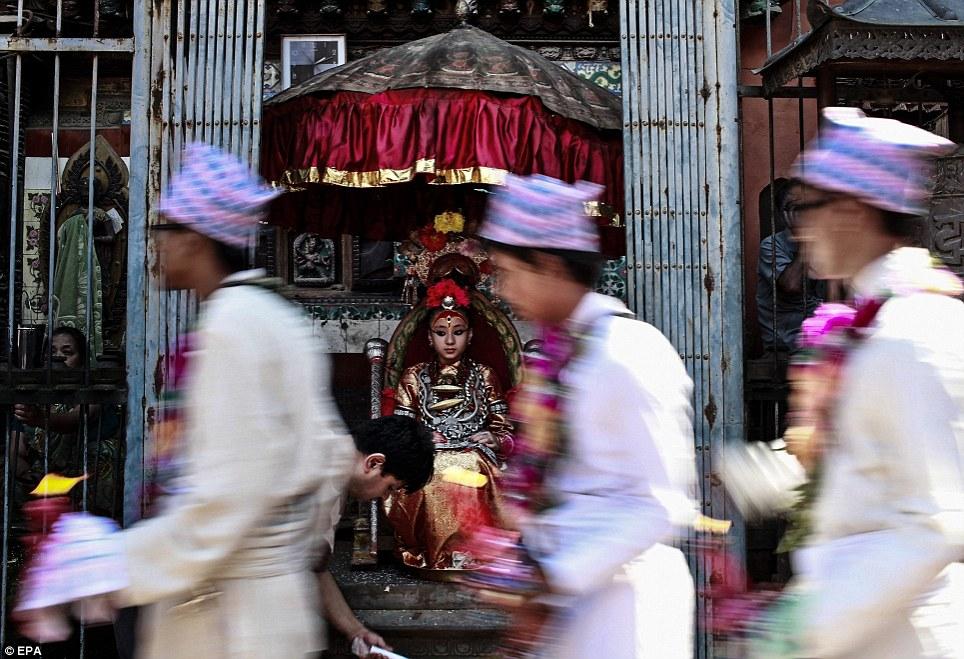 Kumari Samita Bajracharya sits on the traditional throne of Kumari as participants of Matya fesival pass on at Ratnakar Mahavihar in Patan, Nepal, 04 August 2012