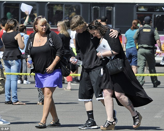 Going home: A family embraces after the shooting at Reynolds High School on Tuesday
