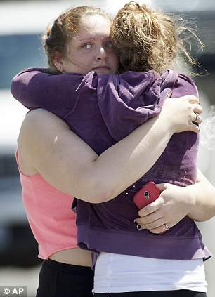 Thankful: Briannah Wilson, 21, (left), and her sister Brittanie Wilson, 19, (right), embrace after students arrived at shopping center parking lot in Wood Village, Oregon after today's shooting at Reynolds High School