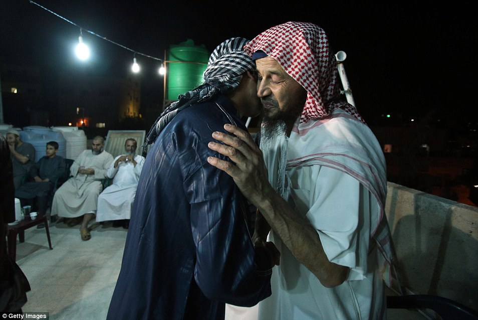 Jihadist Abu Mohammed al-Maqdessi is embraced by guests at his home in Yajuz, Jordan, after serving his sentence for recruiting fighters for the Taliban