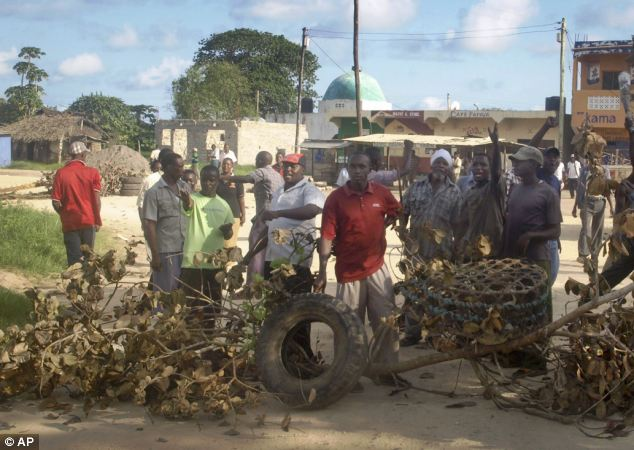 Residents barricade a road as they protest against the recent killings in the village of Kibaoni. Militants linked to Al Qaeda have carried out two massacres in the area - claiming 60 lives
