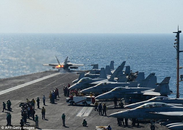 Deployment: F-18 launches off the flight deck of the aircraft carrier USS George H.W. Bush during flight operations in the Arabian Gulf after the ship was deployed into the Gulf in response to the crisis in Iraq