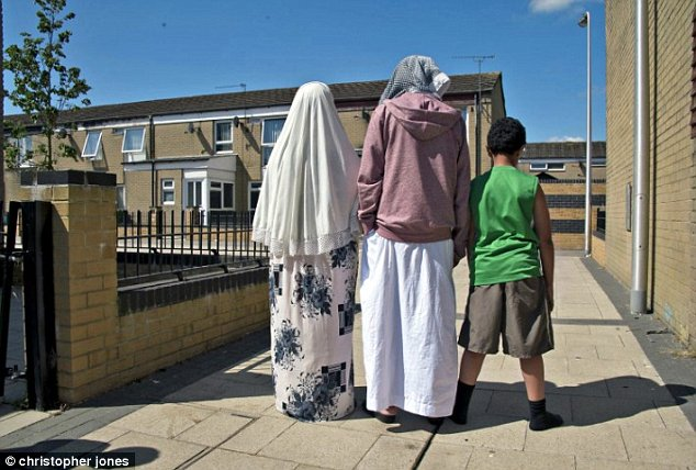 In shock:Nasser and Aseel's parents and youngest brother walk through their Cardiff estate. Their father has said they should be arrested and jailed if they return to the UK
