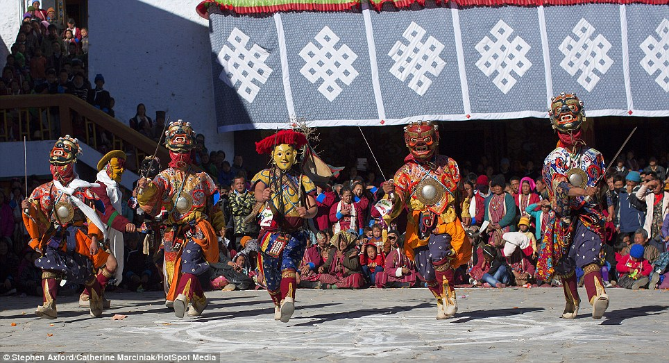 Masked dancers: Five monks perform in brightly coloured robes and traditional Buddhist headpieces