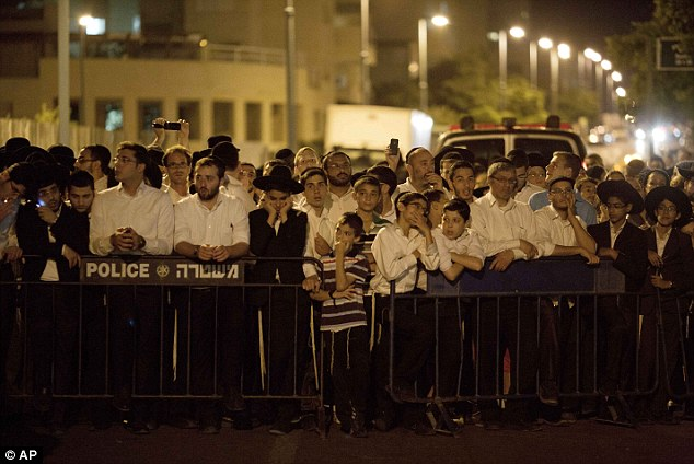 Above, More community members gather outside the Yifrah family home on Monday