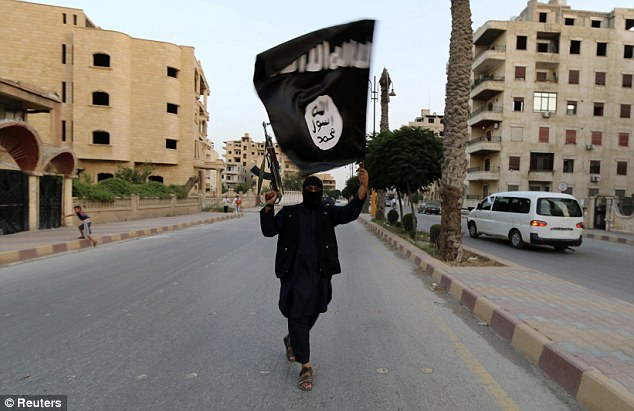Extremist: A gun-brandishing Islamist  loyal to ISIS celebrates the formation  of the Islamic State by waving an jihadist flag in the Syrian city of Raqqa on Sunday. The area is considered the capital of the Islamic State