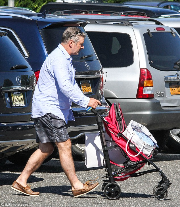 Hands-on dad: The 56-year-old actor pushed his daughter's stroller, looking preppy in a blue button-up teamed with plaid shorts and brown boat shoes