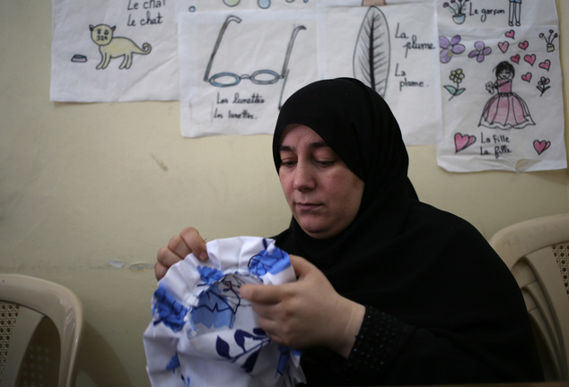 In this photo taken on May 29, 2014, a Syrian refugee woman sews during a class for refugee women obtain crucial training to find jobs in a community center ...