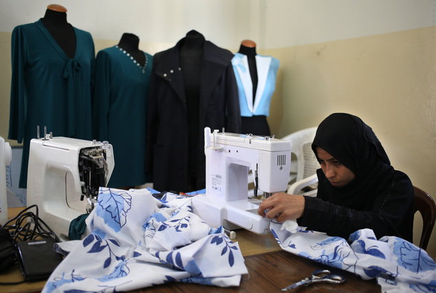In this photo taken on May 29, 2014, a Syrian refugee woman sews aprons during a class for refugee women obtain crucial training to find jobs in a community ...