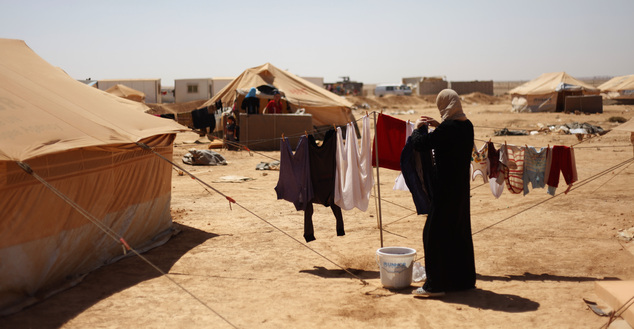 ADVAFILE - In this Sunday, Sept. 2, 2012, file photo, a Syrian refugee woman hangs her families clothes to dry at Zaatari Refugee Camp in Mafraq, Jordan. Acr...
