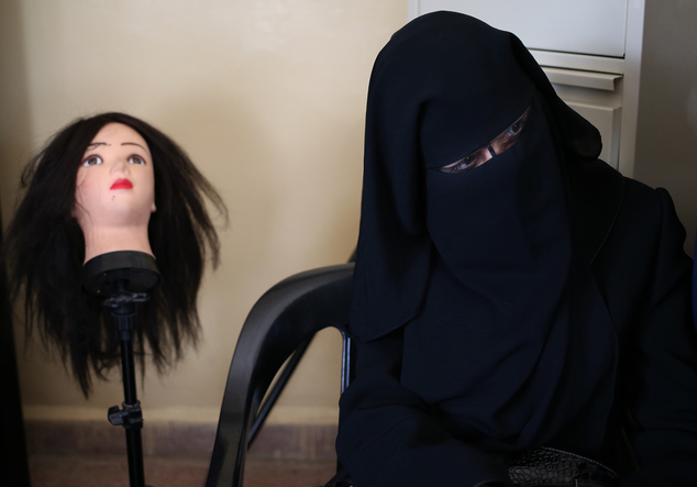 In this photo taken on May 29, 2014, a veiled Syrian refugee woman attends a hair dressing class where women obtain crucial training to find jobs in a commun...