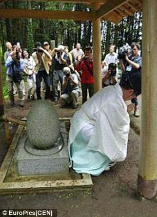 Priest Osamu Hayakawa bending over to touch the 'holy egg' at the shrine