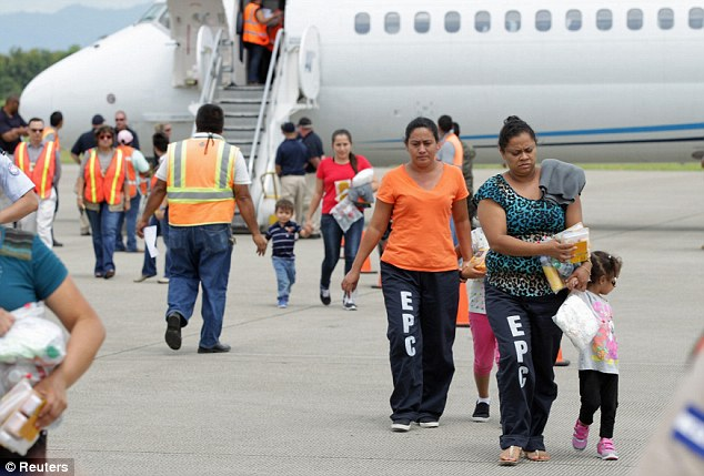 Women and their children walk on the tarmac after being deported from the U.S., at the Ramon Villeda international airport in San Pedro Sula on Monday