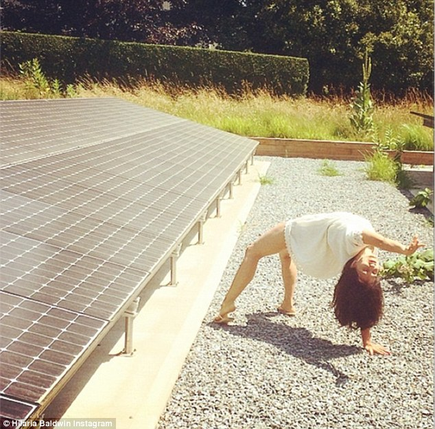 Bright idea: The 30-year-old did a back bend while next to a solar panel on Sunday