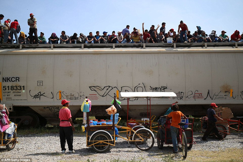Central American immigrants sit atop the so-called La Bestia (The Beast) cargo train, in an attempt to reach the Mexico-US border, in Arriaga, Chiapas state, Mexico on July 16, 2014. AFP PHOTO/ELIZABETH RUIZELIZABETH RUIZ/AFP/Getty Images