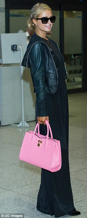 Livening up her look: The blonde beauty carried a baby pink handbag with her all-black ensemble