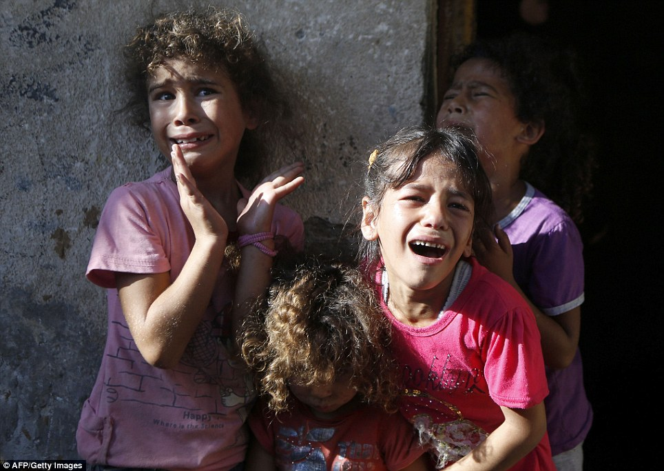 Terror: Young Palestinian children cry during the funeral of four of their relatives in Gaza City this afternoon. The four boys - all from the Bakr family - were killed as Israel shelled a beach earlier in the day