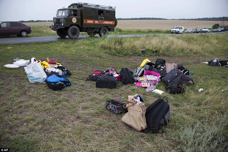 Clear-up operation: Personal luggage is collected at the site of the crashed Malaysia Airlines passenger plane near the village of Rozsypne