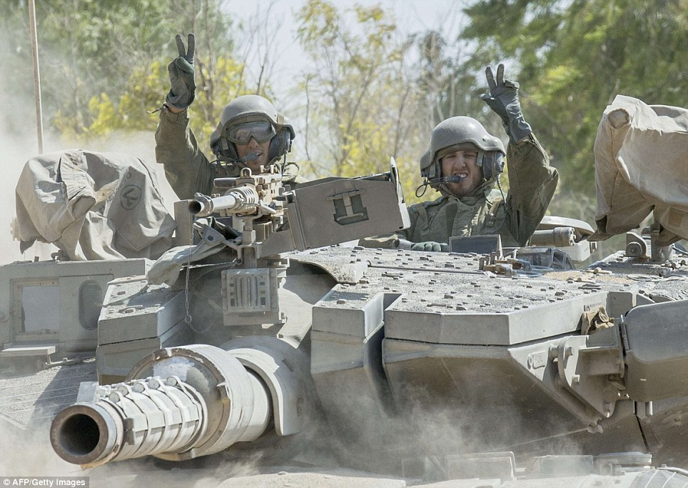 Israeli soldiers flash the victory sign on their armoured personnel carrier (APC) at an army deployment near Israel's border with the Gaza Strip