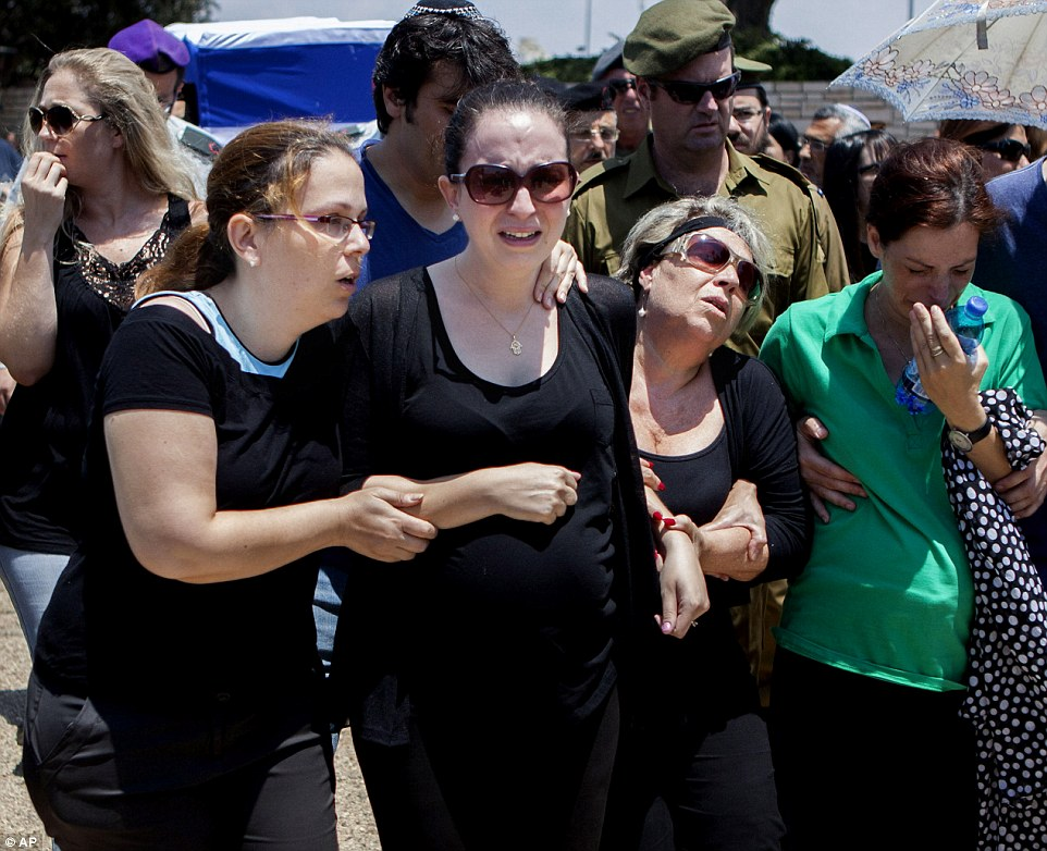 Family and friends mourn during the funeral of Maj. Tzafrir Bar-Or, 32, one of 13 solider's who were killed in several separate incidents in Shijaiya on Sunday, at the military cemetery in Holon, Monday, July 21, 2014. On Sunday, the first major ground battle in two weeks of Israel-Hamas fighting exacted a steep price, killing scores of Palestinians and more than a dozen Israeli soldiers and forcing thousands of terrified Palestinian civilians to flee their devastated Shijaiyah neighborhood, which Israel says is a major source for rocket fire against its civilians. The 13 Israeli soldiers were killed in Shijaiya, in gun battles and rocket attacks. In the deadliest, Gaza fighters detonated a bomb near an armored personnel carrier, killing seven soldiers inside, the army said. In another incident, three soldiers were killed when they became trapped in a burning building, it said. (AP Photo/Dan Balilty)