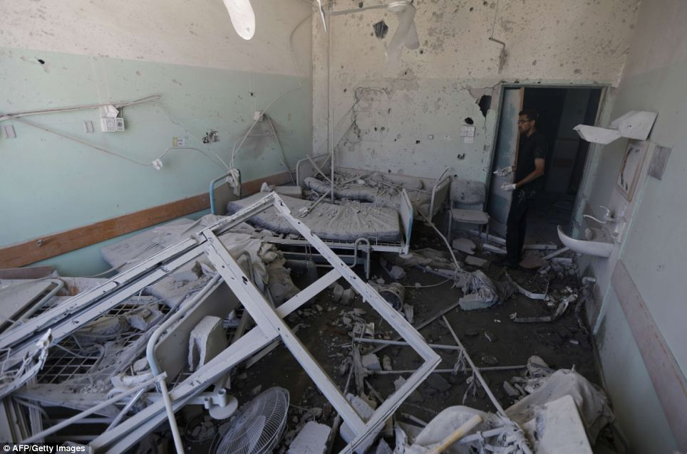 Destroyed: A Palestinian employee inspects damages at the Al-Aqsa Martyrs hospital in Deir al-Balah, in the central Gaza Strip, after the building was shelled today