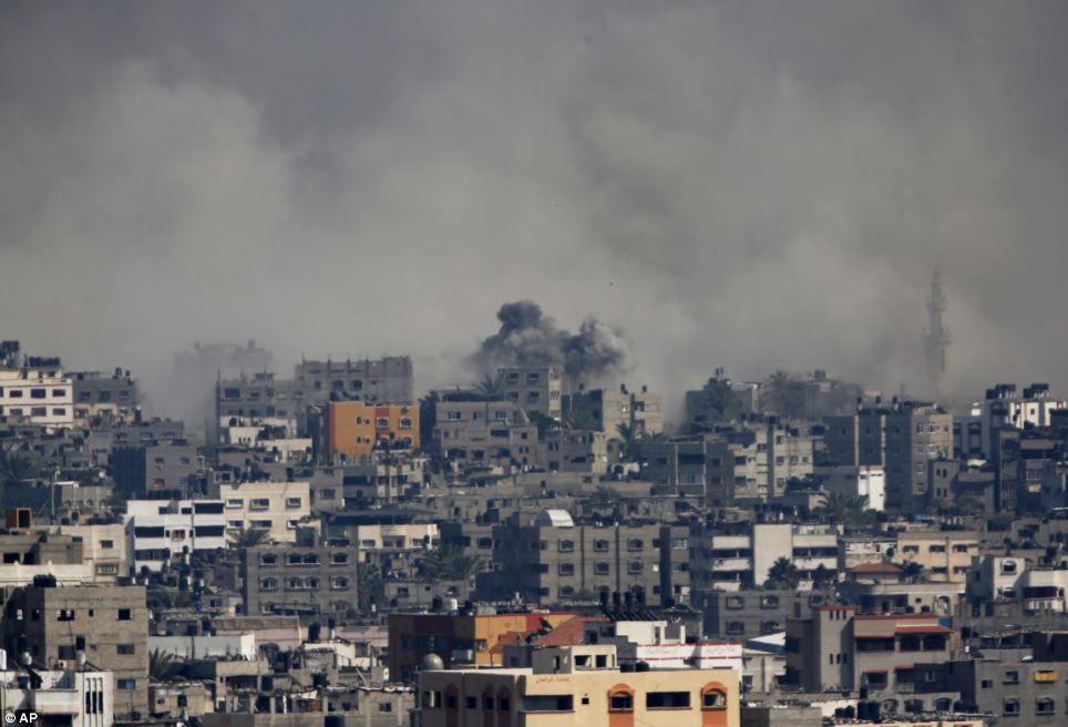 Explosion: Smoke rises after an Israeli shelling at the Shijaiyah neighborhood in Gaza City, today. The top Hamas leader in the Gaza Strip has signalled that the Islamic militant group will not agree to an unconditional cease-fire with Israel, while Israel's defense minister pledged to keep fighting 'as long as necessary', raising new doubt about the highest-level mediation mission in two weeks