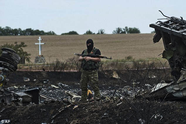 Masked and armed: A pro-Russian fighter guards the crash site of Malaysia Airlines flight MH17 near the village of Hrabove in eastern Ukraine