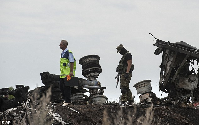 Investigation: Russian president Vladimir Putin has urged separatists (right) to allow international experts (left) access to the crash site