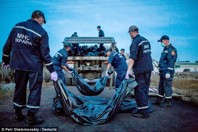 Final indignity: Rescue workers, pictured above, loaded the corpses onto trucks at the crash site in eastern Ukraine, which were then taken to refrigerated train carriages nine miles away